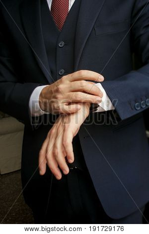 Closeup Of Man's Hands Holding A Watch On The Wirst