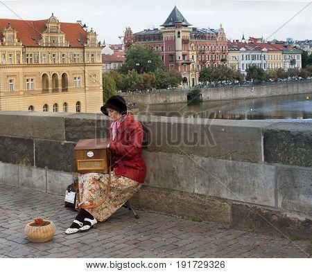 Prague - September 21 2016: an unidentified woman with street organ on Charles Bridge.