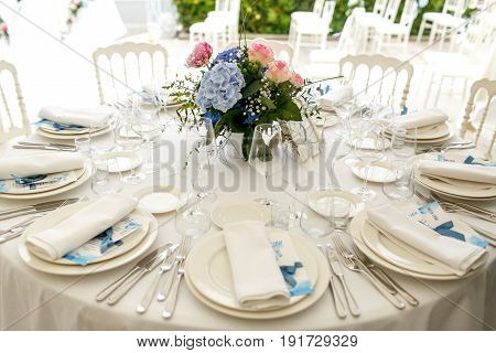 Silver Cutlery And White Crockery Stand On The Round Dinner Table