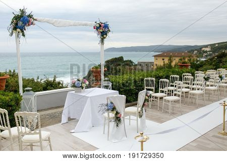 White Wedding Altar Decorated With Blue Flowers Stands In The Front Of Great View On The Sea