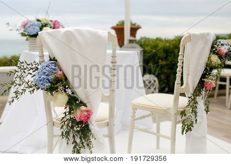 Chairs Covered With White Cloth And Blue Flower Garlands Stand At The Table