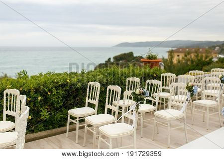 Original White Chairs Stand On The Porch Over The Sea