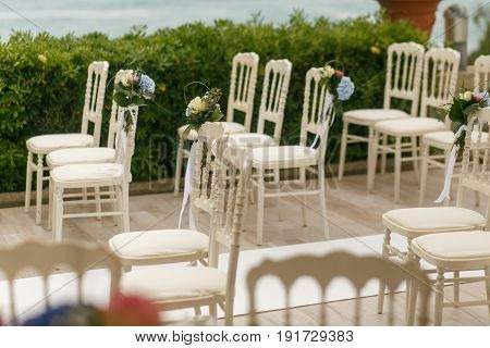 White Chairs Stand On The Different Sides Of The Path To Wedding Altar