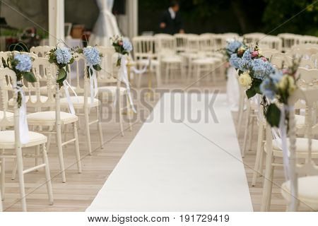 White Path Runs Between The Chairs Decorated With Blue Flowers
