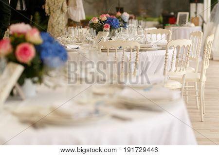 Half-blurred Picture Of White Round Table Served For The Wedding Dinner