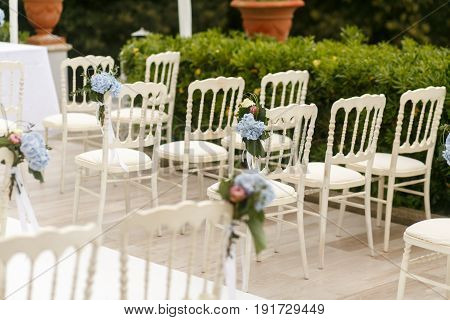 White Chaires Decorated With Blue Hydrangeas Stand In Rays