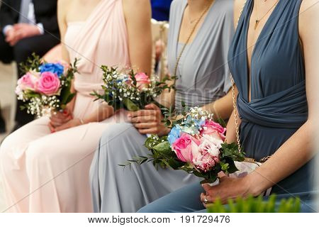 Bridesmaids In Blue, Grey And Pink Dresses Sit In The Ray
