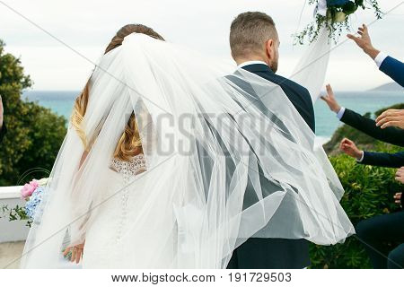 Bride's Veil Blows Around While She Walks With A Groom To Wedding Altar
