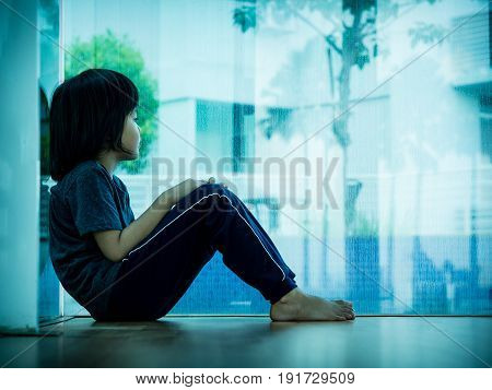 little boy unhappy sad stitting in empty room and tress alone. Sad child concept.