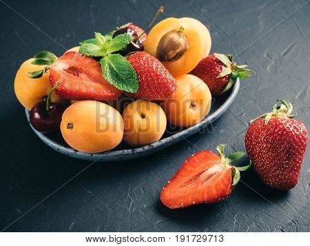 Closeup view of fruits and berries on dark background. Heap of fresh strawberries, blueberries, apricot and mint leaves in trendy plate. Focus on strawberry. Healthy food, superfood, diet, detox concept.
