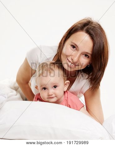 happy family. Mother and baby playing and smiling on white bed with white background