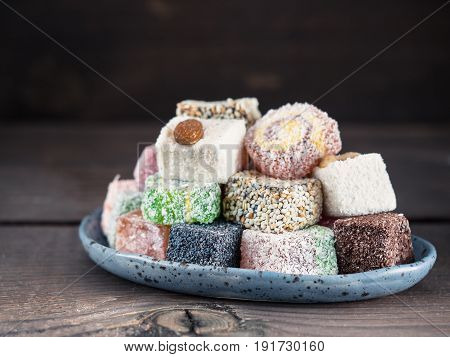 Closeup view of assortment turkish delight in blue trandy plate on dark wooden background. Copy space. Low key