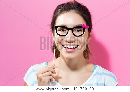 Young woman holding paper party sticks on a solid color background