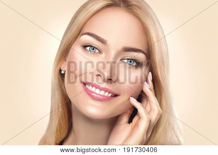 Beauty Woman Face Portrait. Beautiful Spa Girl Touching her Face and smiling. Perfect Fresh Skin. Pure Beauty Model Female looking at camera. Youth and Skin Care Concept. Beige background