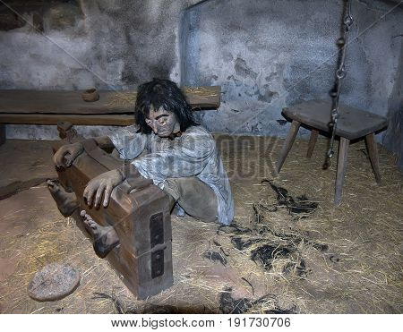 Castle Loket Czech Republic- September 19 2016: prison cell with victim (mannequin) in stocks punishment device