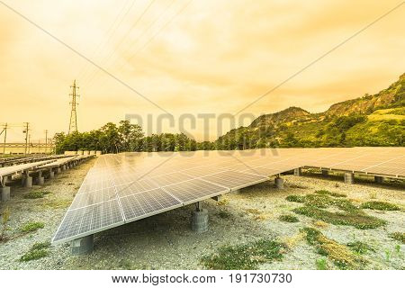 Solar power panels for innovation green energy for life with mountains and sky background.