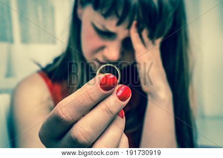 Sad woman is holding wedding ring - divorce concept - retro style