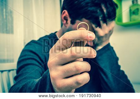 Sad man is holding wedding ring - divorce concept - retro style