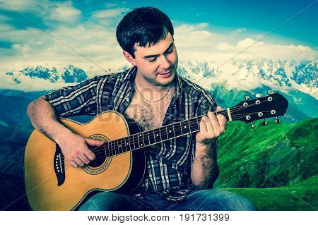Attractiveg man playing acoustic guitar on nature background - retro style