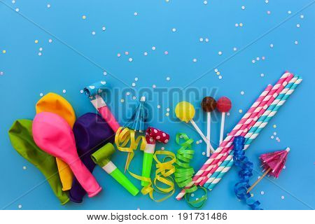 Candy, whistles, streamers, balloons on holiday table. Concept of children's birthday party. View top.