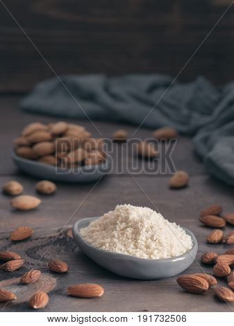 Almond powder in gray trendy plate and almonds on dark wooden table. Almond flour and peeled kernel almonds. Copy space. Vertical.