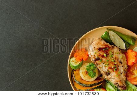 Homemade chicken breast barbecue on wood plate served with grilled vegetable. Delicious chicken barbecue and grilled vegetables for lunch or dinner. Roast chicken breast or barbecue on granite table. Top view chicken barbecue or pork steak.