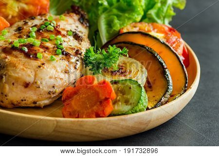 Homemade chicken breast barbecue on wood plate served with grilled vegetable. Delicious chicken barbecue and grilled vegetables for lunch or dinner. Roast chicken breast or barbecue on granite table. Piece of chicken barbecue or pork steak.