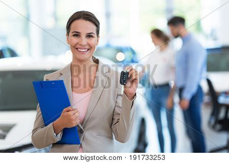 Female car dealer standing in showroom