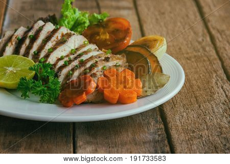 Sliced chicken breast barbecue on white plate served with grilled vegetable. Delicious chicken breast steak and salad for dinner. Homemade chicken breast barbecue on wood table for background. Chicken barbecue or pork steak for dinner.