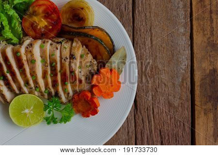 Sliced chicken breast barbecue on white plate served with grilled vegetable. Delicious chicken breast steak and salad for dinner. Homemade chicken breast barbecue on wood table for background. Chicken barbecue or pork steak in top view.