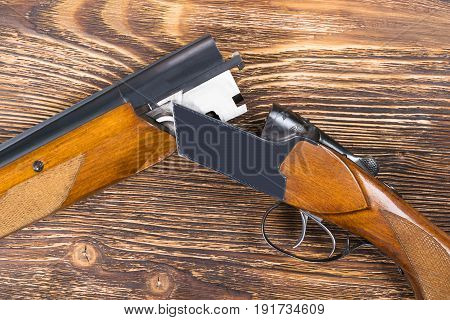 An open rifle with cartridges rests on a wooden table