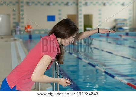Trainer Woman Holding A Stopwatch On Poolside And Conducts Training