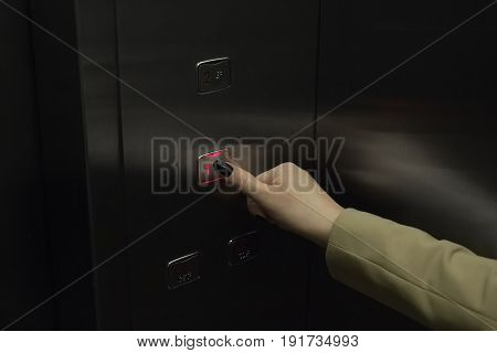 Female finger presses the button on the elevator to go to the first floor.