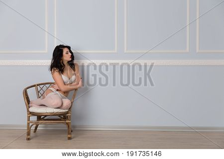Sexy Young Brunette Woman In White Erotic Lingerie Sitting On Chair.