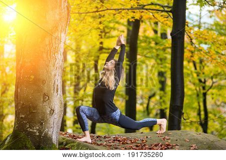 Sporty Young Woman Is Practicing Yoga And Doing Asana Virabhadrasana 1 In The Autumn Park On The Big