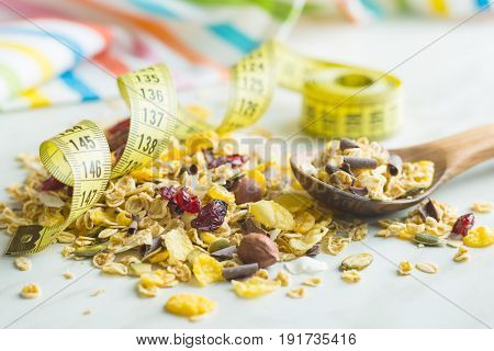 Tasty homemade muesli with nuts in bowl with measuring tape. Diet concept.