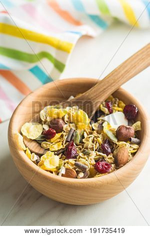 Tasty homemade muesli with nuts in wooden bowl.