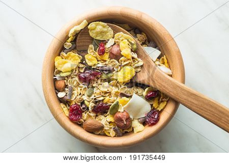Tasty homemade muesli with nuts in wooden bowl. Top view.