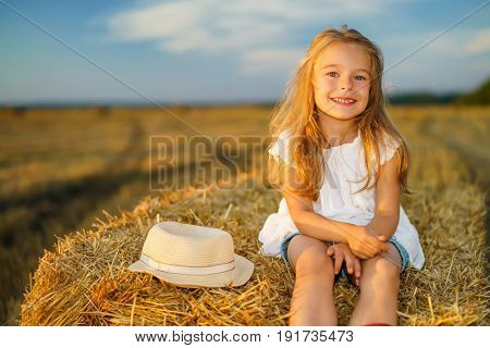 Happy little girl in a field with hay rolls at sunset