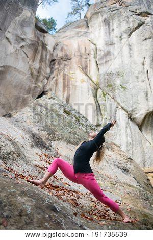 Happy Young Woman Is Practicing Yoga And Doing Asana Virabhadrasana 1 Outdoors. Huge Rocks On The Ba
