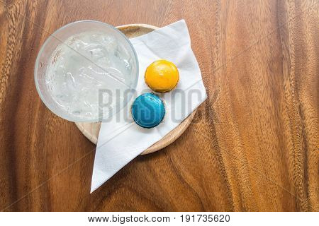 Welcome drink set with fresh ice-water blue and orange colors magaroons and white nepkin in wooden tray on wooden table.