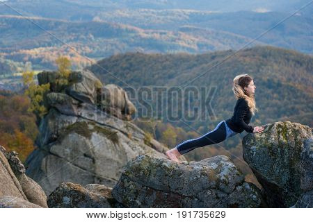 Young Fit Female Is Practicing Yoga And Doing Asana Urdhva Mukha Shvanasana On The Top Of The Mounta