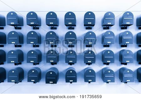 Mailboxes in residential for informations and news with room number toned in blue.