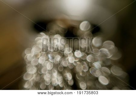 Abstract gold bokeh with blur and flare. Elegant jewelry with bokeh defocused lights.
