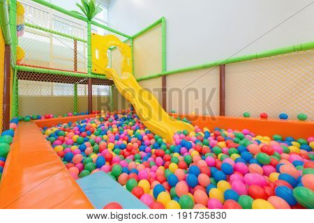 Children's playground with yellow plastic slider and colorful plastic balls in pool.