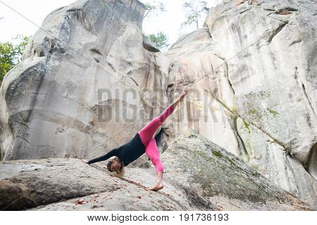 Young Slim Woman Is Practicing Yoga And Doing Asana Adho Mukha Shvanasana In The Nature. Huge Rocks