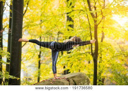 Yoga Outdoors - Sporty Fit Female Doing Asana Virabhadrasana 3 In Autumn Park On The Big Boulder
