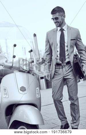 Successful dedicated young businessman on street wearing suit tie and sunglasses going to ride a scooter.