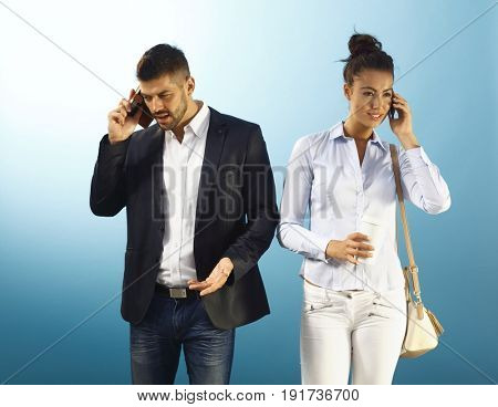 Young businesspeople using mobilephone over blue background.