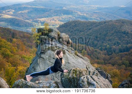 Attractive Fit Woman Is Practicing Yoga And Doing Asana Urdhva Mukha Shvanasana On The Top Of The Mo